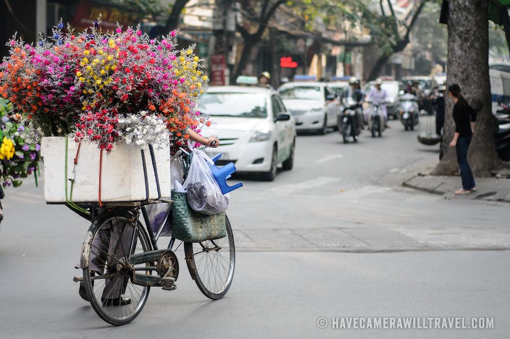 A local flower vendor dodges the frantic traffic of Hanoi's Old Quarter.