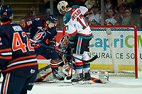 KELOWNA, CANADA - DECEMBER 29: Alex Swetlikoff #17 of the Kelowna Rockets is checked by Quinn Schmiemann #25 as Dylan Ferguson #31 of the Kamloops Blazers defends the net during second period on December 29, 2018 at Prospera Place in Kelowna, British Columbia, Canada.  (Photo by Marissa Baecker/Shoot the Breeze)
