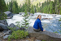 A portrait of anmiddle-aged Caucasian woman smiling while sitting above Icicle Creek.  Washington Cascades, USA.