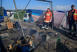 © Licensed to London News Pictures. 25/10/2016. Calais, France.  A team of firemen put of a fire started at a living tent in the migrant and refugee camp in Calais, known as the 'Jungle'. French authorities have moved thousands of refugees and migrants living at the makeshift living area on the French coast, with some still refusing to leave. . Photo credit: Ben Cawthra/LNP