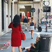 Milan, Italy - July 14th, Woman carrying a luxury carrier bag passing by a beggar in the luxurious center of Milan Italy