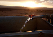Running water for livestock at sunset.