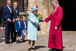 Windsor, UK. 21st April 2019. The Queen shakes hands with the Dean of Windsor, the Rt Revd David Conner KCVO, following the Easter Sunday service at St George's Chapel in Windsor Castle.