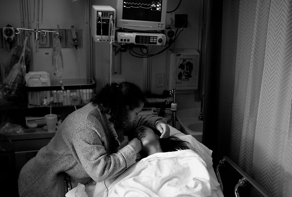 "2/13/2009 Baltimore, MD-  Lani Dickinson, 14, is comforted by her mother Julie Bell in a recovery room at Johns Hopkins Hospital after she underwent surgery for the ""revision of her transhumeral amputation.""  Lani was born in China with a congenital defect and adopted by an American family.  Despite her disability, she trains hard as a ballerina and would like to someday be a professional dancer.  Photo by Lisa Hornak"