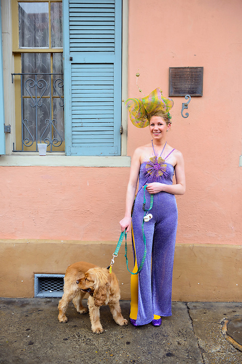 A young woman dressed for Mardi Gras stands with her English cocker spaniel in the French Quarter of New Orleans, Louisiana.