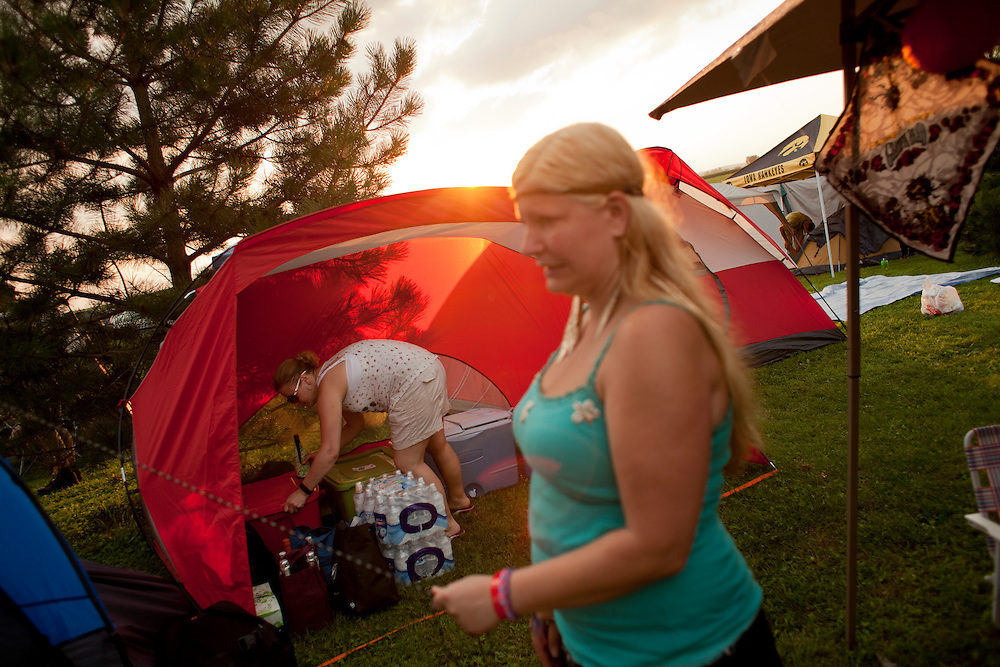 Jana Rose Summers (foreground) and Jen Wilson set up camp with their friends at Camp Euforia on Thursday, July 16, 2015. The three-day music festival is held at Jerry Hotz's 120-acre farm north of Lone Tree in Johnson County and has grown from a small gathering to a well-organized fest that regularly draws about a thousand tent and RV campers.