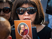16 DECEMBER 2015 - BANGKOK, THAILAND: A woman holds a photo of Somdet Phra Nyanasamvara, Thailand's Supreme Patriarch, during the Patriarch's funeral. He died Oct. 24, 2013. He was ordained as a Buddhist monk in 1933 and appointed as the Supreme Patriarch in 1989. He was the spiritual advisor to Bhumibol Adulyadej, the King of Thailand when the King served as a monk in 1956. Tens of thousands of people lined the streets during the procession to pray for the Patriarch.     PHOTO BY JACK KURTZ