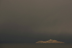 A gap in the clouds highlights the island of Inchkeith in the Firth of Forth off Edinburgh as winter clouds behind all but obscure Fife. © Jon Davey/ EEm