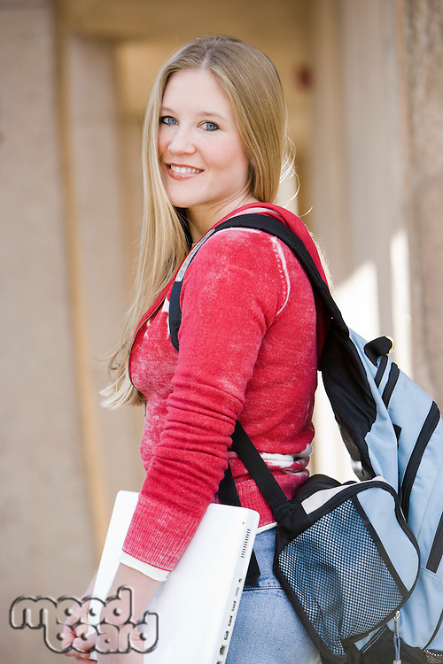 Young student with laptop and backpack