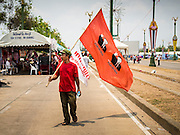06 APRIL 2014 - BANGKOK, THAILAND:  A Red Shirt supporter carries a flag into a rally on the edge of Bangkok Sunday. Red Shirts and supporters of the government of Yingluck Shinawatra, the Prime Minister of Thailand, gathered in a suburb of Bangkok this weekend to show support for the government. The Thai government is dealing with ongoing protests led by anti-government activists. Legal challenges filed by critics of the government could bring the government down as soon as the end of April. The Red Shirt rally this weekend was to show support for the government, which public opinion polls show still has the support of most of the electorate.  PHOTO BY JACK KURTZ