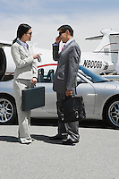 Mid-adult businesswoman and mid-adult businessman standing in front of convertible and talking.