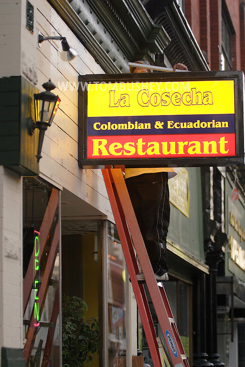 Middletown, NY - A worker on a ladder installs a sign for a Colombian and Ecuadorian restaurant on North Street on Sept. 15, 2007.