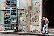 The body language of the man having a morning cigarette on the streets of Havana, Cuba reinforces the story told by the layers and layers of peeling paint on the wall.