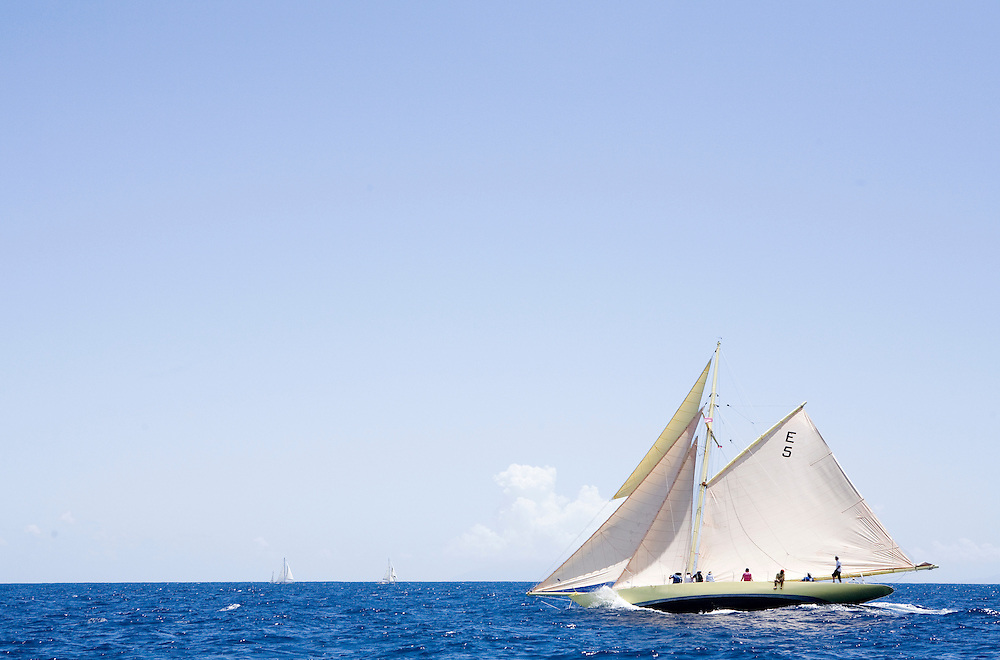 The gaff rigged cutter whose name is SY Kate sailing along the shore line during the 2008 Antigua Classic Yacht Regatta . This race is one of the worlds most prestigious traditional yacht races. It takes place annually off the costa of Antigua in the British West Indies.