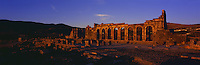 Sunset falls over Basilica and the Temple of Saturn at the ruins of the ancient Roman city of Volubilis Dates from the 2nd and 3rd centuries AD A UNESCO world heritage site Sunset silhouettes the curved archways of the Basilica , Meknes , Morocco