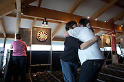 Winner and loser darts players hug affectionately after a preliminary round of ladies darts during tournament game.
