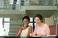 Two mid-adult female office workers having break