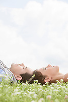Side view of young couple sleeping on grass against sky