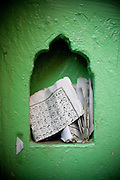 Old Delhi. A green wall with pices of qu'ran or other islamic writings.