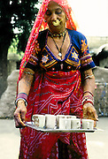 Ancient village woman dressed in her best graciously serves a tray of tea.  Large nose ring, bracelets, embroidered blouse, red veil.