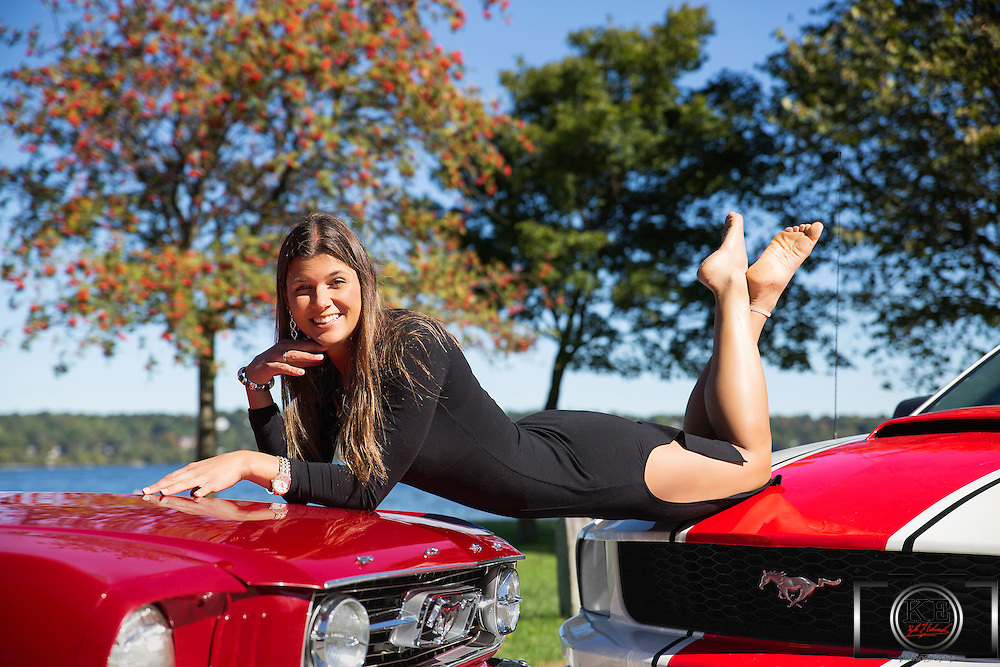 A young lady in a black dress, laying on two Mustangs