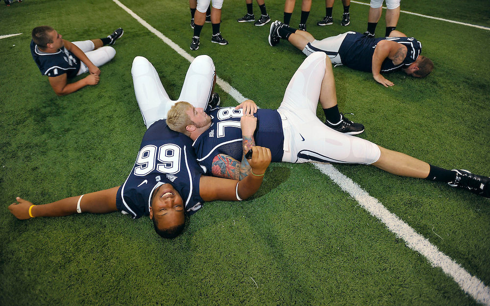 Connecticut's Mathieu Olivier (66) and Zach Hurd (78) relax with teammates while waiting to be photographed during the NCAA college football team's media day in Storrs, Conn., Monday, Aug. 16, 2010. (AP Photo/Jessica Hill)