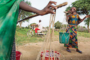 Girls balance buckets of water on both ends of a stick as they prepare to carry them back home from a UNICEF-sponsored pump in the village of Game, Guera province, Chad on Tuesday October 16, 2012.