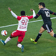 Nov 8, 2015; Harrison, NJ, USA; D.C. United forward Fabian Espindola (10) kicks the ball while being defended by New York Red Bulls defender Kemar Lawrence (92) during the first half of the MLS Playoffs at Red Bull Arena. Mandatory Credit: William Hauser-USA TODAY Sports