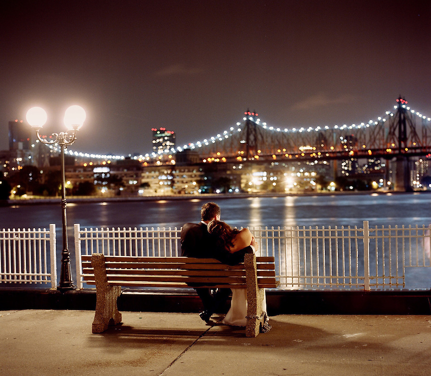 Romantic photo of Bride and groom sitting on park bench at night looking across the East River at the 59th St Bridge lights and the Manhattan skyline