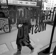 As a London double-decker bus goes by with an ad featuring a pair of eyes, an anonymous passer-by looks into the window a clothing retailer in the City of London.
