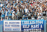 CHARLOTTE, NC - SEPTEMBER 18:  Carolina Panthers fans cheer their team in front of an NFL Hurricane Relief Weekend sign intended to generate funds for those affected by Hurricane  Katrina during a week two game against the New England Patriots at Bank of America Stadium on September 18, 2005 in Charlotte, North Carolina. The Panthers defeated the Patriots 27-17. ©Paul Anthony Spinelli