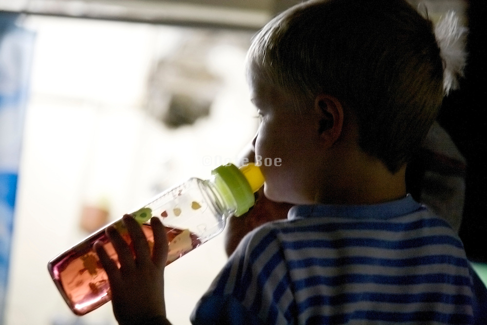 little child with bottle indoors