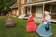 Old Bethpage, New York, U.S. 31st August 2013.  JANE HEILIG of Bethpage, in taupe, and sisters, PATRICIA JOSEPH of College Point in red, and JULIETTE FOX of Hicksville in blue, are wearing Civil War era style clothing and are members of the Old Bethpage Village Dancers which danced throughout the Olde Time Music Weekend at Old Bethpage Village Restoration, where popular music of the American Civil War period was performed, and visitors learned traditional 1800's contradances. They are at the porch of 12 Lawrence House, which originally was located across the street from the home the sisters were born at.