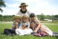 MICHELE WALKER (rear) of Coram; (L to R) ROBERT WALKER, 4; JULIAN LYNN ZOLL 6, of Levittown; and MADELYN WALKER, 7, wear clothes of American Civil War era while portraying family members of Union soldiers at Camp Scott re-creation, at Old Bethpage Village Restoration, to commemorate 150th Anniversary of American Civil War, on Saturday, July 21, 2012, in Old Bethpage, New York, USA.