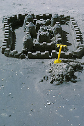 Sand castle with childs toy yellow rake on beach at shore, Stone Harbor, NJ.
