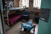 An 'enhanced' prisoner doing press ups in his room on H wing at the Young Offenders Institution  in Aylesbury, United Kingdom.  Under the Incentives and Earned Privilege Scheme, prisoners in the U.K. can earn extra privileges for good behaviour such as wearing their own clothes, having televisions in their cells, and having more free time to socialise.  They are often housed together in their own wing.  There are three levels of earned privileges - Basic, Standard and Enhanced.