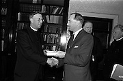 """21/5/1965<br /> 5/21/1965<br /> 21/5/1965<br /> <br /> President de Valera recived an inscribed mathematic textbook """"Matamatic na h'ard Teistimeireachta"""" from the author An Br. Tomás Ó Catnain, Mount Sion Waterford.<br /> <br /> An Br. Tomás Ó Catnain and Mr. George Colley T.D shaking hands at the event"""