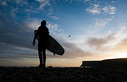 © Licensed to London News Pictures. <br /> 09/03/2015. <br /> <br /> Saltburn, United Kingdom<br /> <br /> Surfer Tom Davis stands on the beach looking out to sea before going out for an early morning surf at sunrise at Saltburn by the Sea.<br /> <br /> Photo credit : Ian Forsyth/LNP