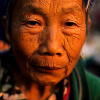 Elderly Akha woman poses at morning market, Muang Singh, Laos