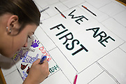 Maddy Gilmore, a member of We Are First, a group of first generation college students, decorate a banner for the Homecoming parade in the First Scholars House on Tuesday, October 6, 2015. Photo by Kaitlin Owens