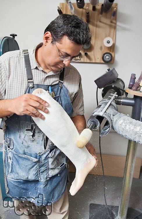 Mature male worker buffing prosthetic limb