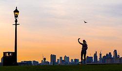 London, August 16 2017 . A woman takes a selfie on Primrose Hill as London wakes up to a glorious sunrise © Paul Davey.