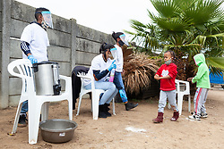 """Young children sanitize their hands as they line up for food parcels at a """"Safe Zone"""" in Vanwyk'svlei, Wellington, Western Cape, South Africa.(Picture: JULIAN GOLDSWAIN)"""