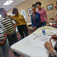 Artist Arni Anderson, right, gives students in the Aberdeen Park and Recreation Department's winter break program tips on painting a vase of flowers.