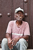 An elderly Cuban man sits with a cigar in Old Havana.