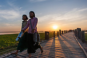 Two girls strolling on U Bein bridge at dusk (Amarapura, Myanmar)