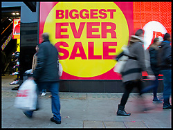 Boxing Day Shoppers walk past a Sale sign on a busy Oxford Street in Central London as bargain hunters shop in the  Boxing Day Sales, Monday December 26, 2011. Photo By Andrew Parsons/i-Images