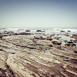 Crystal Cove Rock formations and tde pools picture. Crystal Cove State Park is located along the Pacific Ocean in Laguna Beach and Newport Beach in Southern California. Photo has retro vintage beach tone. Image Copyright © Paul Velgos All Rights Reserved.