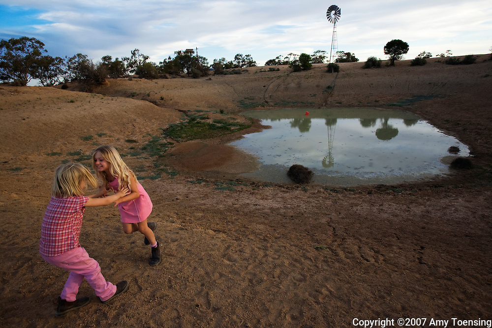 IVANHOE, NSW, AUSTRALIA - FEBRUARY 10: Natalie and Samantha Turner play near a farm dam with low water on a trip with their dad to clean out watering troughs and check on windmills on their farm February 10, 2008 in Ivanhoe, New South Wales, Australia. The Turners, like many farm families in the Murray-Darling Basin have had to move most of their livestock to other regions of Australia because their own land is too dry to produce feed after years of drought. The Murray-Darling Basin of Australia has been plagued with severe drought since the late 1990's. (Photo by Amy Toensing/ Reportage by Getty Images).... _________________________________<br />