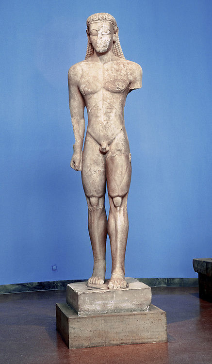 A larger-than-life-size kouros statue from 600 BC stands in the National Archaeological Museum, in Athens, Greece, Europe. A kouros is a representation of male youth dating from the Archaic Period in Greece 800-480 BC and found in Greek sanctuaries of Apollo, in commemorative tombstones of the deceased, and in memorials (like trophies) for victors of games. Kouros sculpture in Greece appears directly influenced by Egyptian monumental sculpture such as the figure of Horus. Greece and Egypt traded goods and cultural influences since 650 BC.